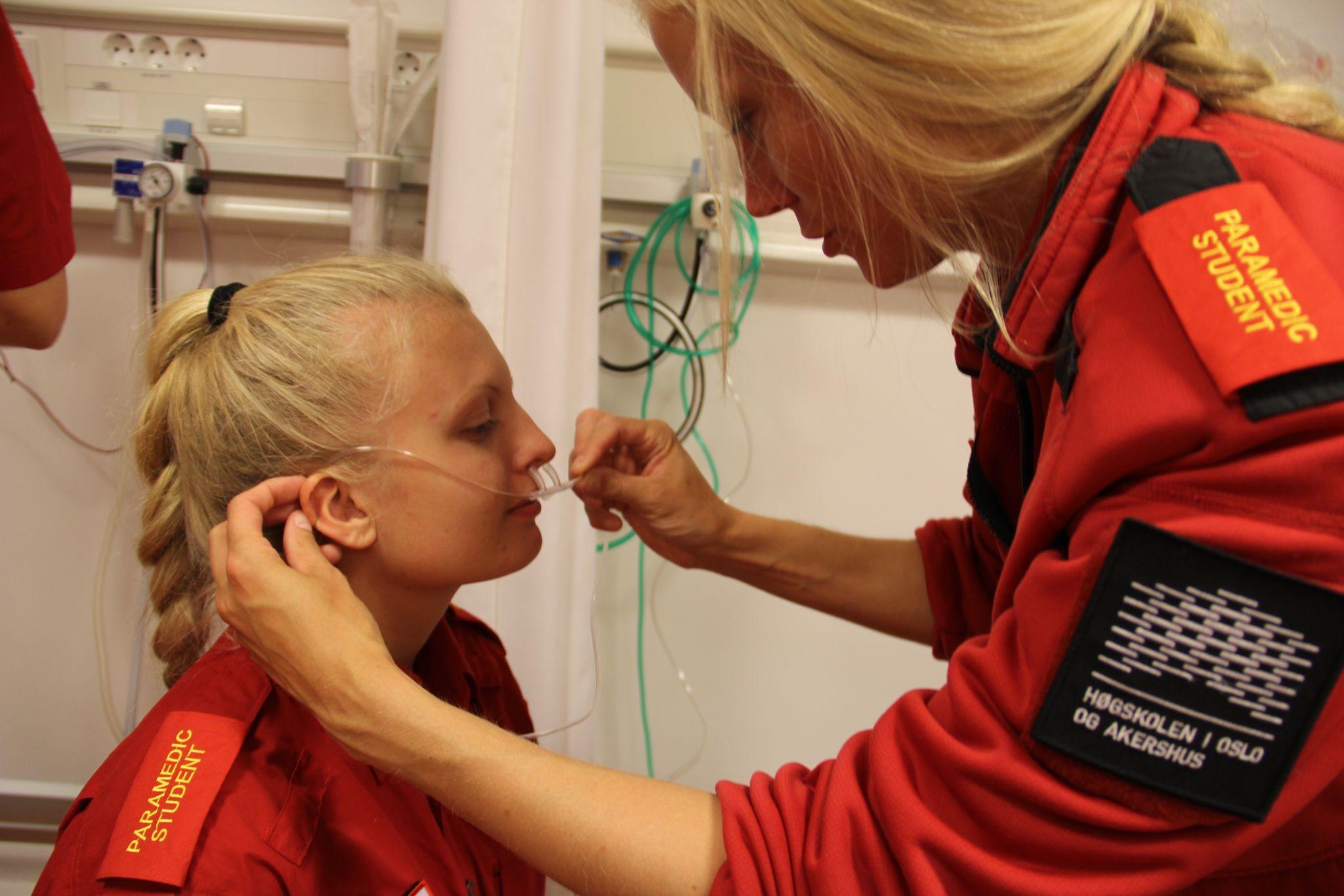 eori og praksis i luftveishåndtering på bachelor i prehospitalt arbeid: Studentene prøver ut nesegrime og maske, slik at de vet hvordan det kjennes ut for pasienten. Fra venstre: Thea Brattås Holte og Ina Dahl.