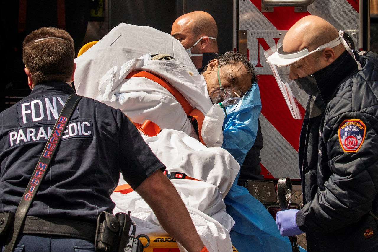 New York City Fire Department (FDNY) Ambulansepersonell med ymse smittevern- utstyr løfter en mann inn i ambulansen under det pågående utbruddet av covid-19 i Brooklyn 16. april, 2020. REUTERS/Lucas Jackson /NTB scanpix