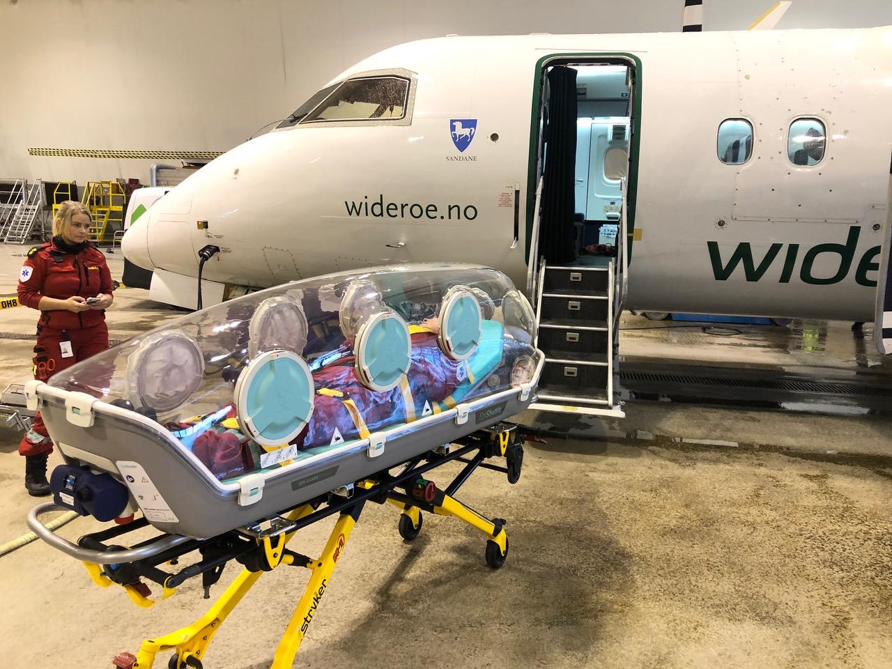 Widerøes Dash 8 - 100 og smittevernkuvøse. Foto: Luftambulanseavdelingen, Universitetssykehuset Nord-Norge HF.