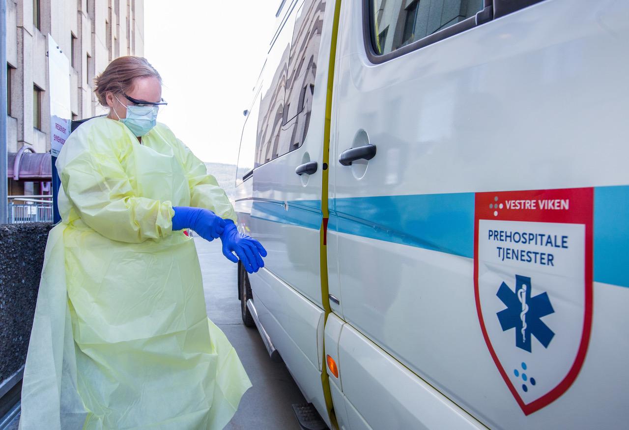 Når akuttambulansen er til dekontaminering må transportambulansen tas i bruk. Martine tar på seg smittevernutstyr før de skal hente en pasient. ©Fredrik Naumann/Felix Features