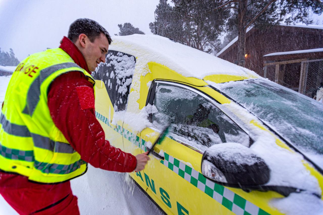 HJEMMEVAKT: Snøbørsting av ambulanse. Vinteren er lang i Finnmark, og ikke alle har en garasje bilen kan stå i når den er hjemme. Foto: Alf Ove Hansen